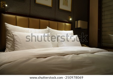 Night scene in hotel room, nightstand with lamp - stock photo