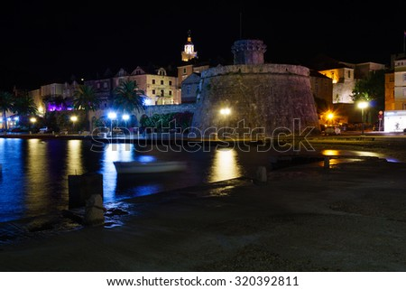Night scene in the old town (west side), with the walls, houses, boats, in Korcula, Croatia - stock photo