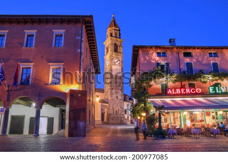 Night scene in the resort town of Ascona, Ticino, Switzerland featuring the belfry of the Parish Church of Ss. Piedro and Paolo, behind the waterfront family-run restaurants. - stock photo