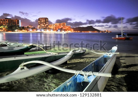 Night scene of a group of outrigger canoes on the beach with Diamond Head - stock photo
