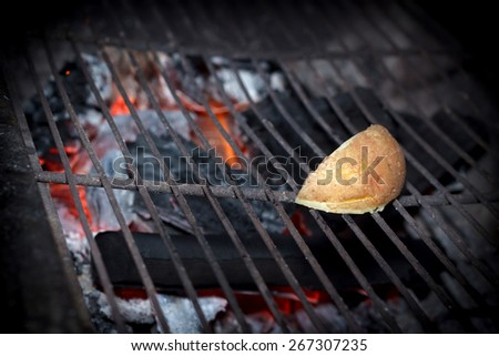 Night scene of cooking potato on grill, shallow DOF - stock photo