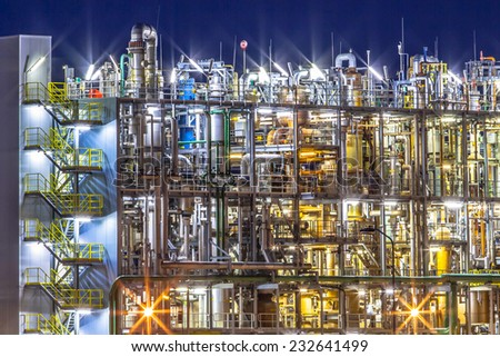 Night scene of detail of a heavy Chemical Industrial plant with mazework of pipes in twilight - stock photo