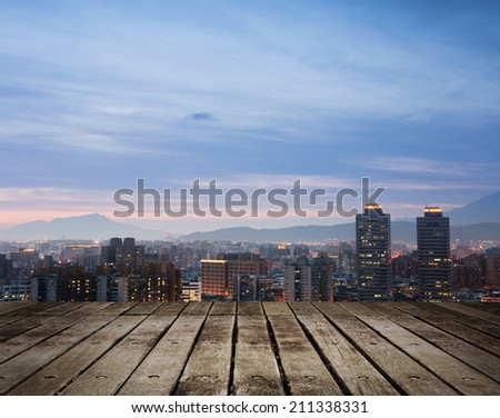 Night scene of modern city under blue and dramatic sky in Taipei, Taiwan, Asia. Focus on wooden floor. - stock photo