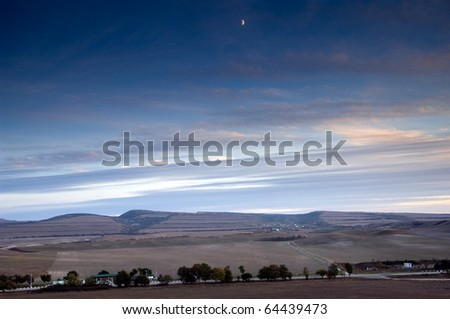 Night scene of mountains with clouds and moon - stock photo