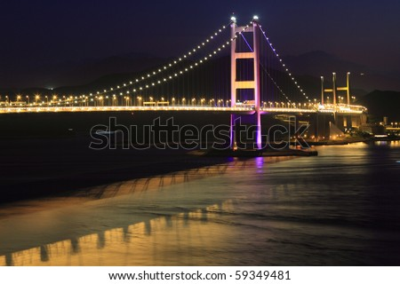 night scene of Tsing Ma bridge and reflection in Hong Kong, key infrastructure leading to the international airport - stock photo