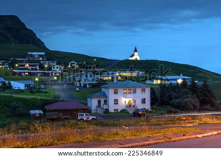Night scene of Vik (Vik i Myrdal), the southernmost village in Iceland with it's church overlooking the sparse houses and a bed and breakfeast. - stock photo
