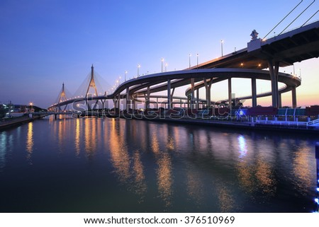 Night scenery of Bhumibol suspension Bridge in Bangkok Thailand, also known as the Industrial Ring Road Bridge over Chao Phraya River, with beautiful reflections on smooth water in evening twilight - stock photo