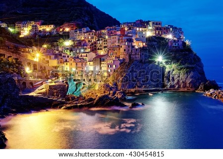 Night scenery of Manarola on vertical cliffs by the rocky coast with beautiful lights reflecting on sea water, an amazing village in Cinque Terre National Park, Liguria, Italy, Europe (Long Exposure) - stock photo