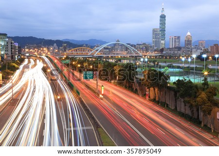 Night scenery of Taipei City, Taipei 101,Xin-Yi District and downtown area with MacArthur Bridge and car trails on Dike Avenue ~ Romantic cityscape of Taipei at dusk by riverside :long exposure effect - stock photo