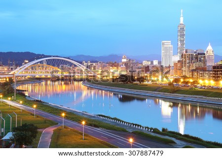 Night scenery of Taipei City with beautiful reflections of skyscrapers and bridges on smooth water by riverside at dusk ~ Cityscape of Taipei 101, Keelung River, Xinyi District & downtown in twilight - stock photo