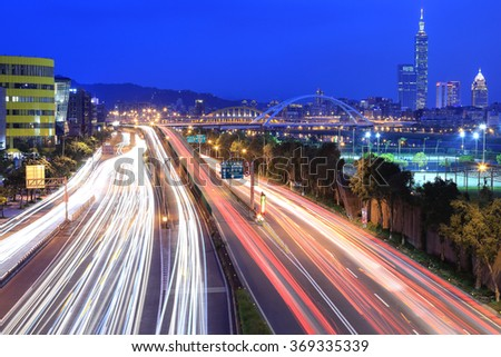 Night scenery of Taipei City, with Taipei 101 Tower in XinYi District, downtown area with arch bridges and car trails on Dike Avenue ~ Romantic cityscape of Taipei at dusk by riverside (long exposure) - stock photo