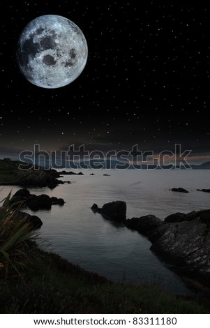 night scenic view in kerry ireland of rocks and sea with mountains against a beautiful blue cloudy sky - stock photo