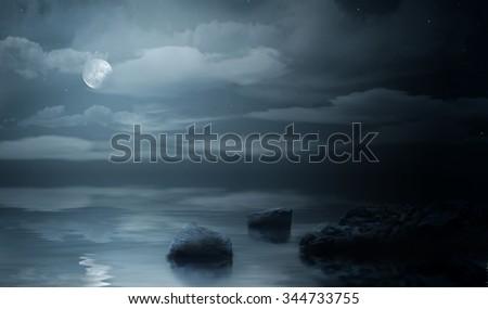 Night sea under cloudy sky - stock photo