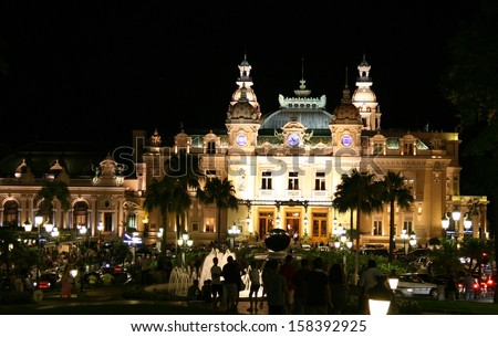 Night shot of a floodlit Monte Carlo Casino with fountains and people in silhouette. Shows a bustling atmosphere. - stock photo