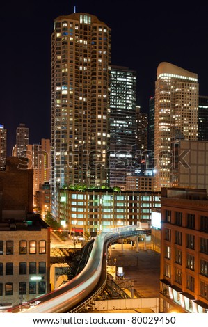 """Night shot of Chicago downtown with motion blurred elevated """"L"""" train. - stock photo"""