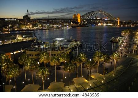 night shot of circular quay in sydney; harbour bridge in background - stock photo