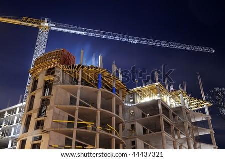 night shot of construction equipment at building site - stock photo