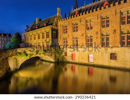 Night shot of historic medieval buildings along a canal in Bruges, Belgium - stock photo