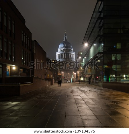 Night shot of people walking in a street leading to St Paul's cathedral in London, capital of the united kingdom - stock photo