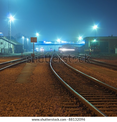 Night shot of railway station with curving track and passing train in background - stock photo