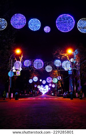 Night shot of street decorated with multicolor christmas lights garlands - stock photo