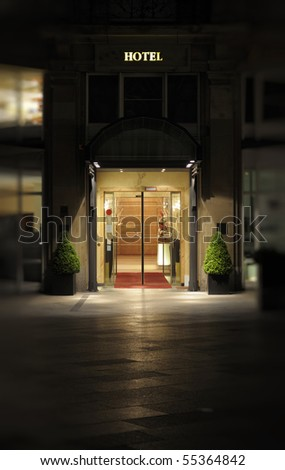 Night shot of the entrance and facade to a luxury hotel. - stock photo