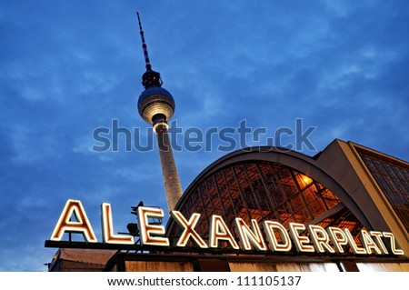 Night shot of the train station Berlin Alexanderplatz with the famous TV tower  in the background.
