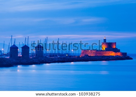 Night shot of the windmills and lighthouse at Mandraki harbour Rhodes Greece.