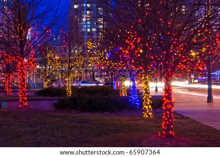 Night shot of trees on street decorated with multicolor christmas lights garlands - stock photo
