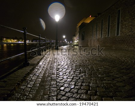 Night shot of wet cobblestone road with glares from lamp in Maastricht, Netherlands. - stock photo