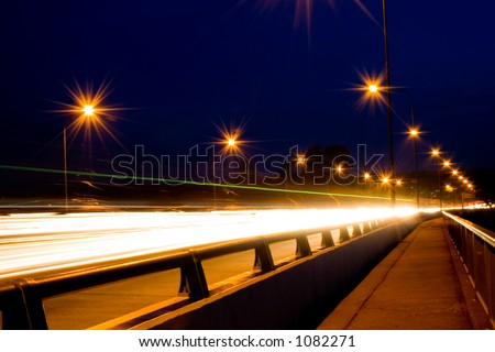 Night-shot on a highway bridge, juxtaposed with a relatively calm pedestrian path contrasting against the high speed road.