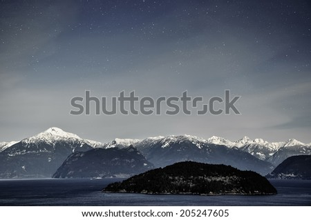 Night sky and stars over snow capped mountain - stock photo