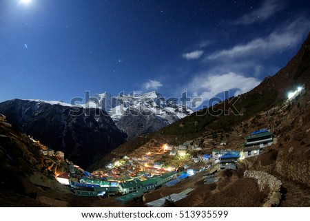 Night sky and stars passing by behind mountain Kongde Ri, Namche Bazaar village. Nepal.