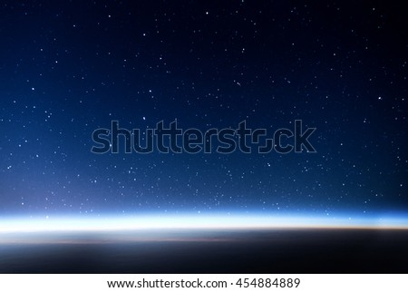 Night sky full of stars and sunrise on the horizon of the Earth on the background. Concept of the space view. - stock photo