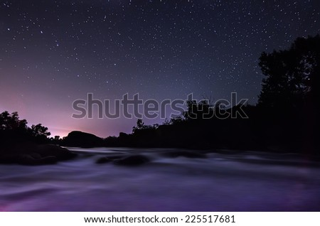 Night sky with lot of shiny stars, rocks and fast flowing water are at front - stock photo