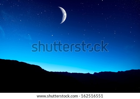 Night sky with moon over mountain - stock photo