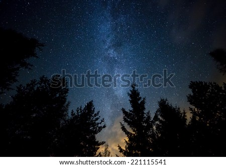 Night sky with the Milky Way over the forest and trees. The last light of the setting Sun on the bottom of the image. - stock photo