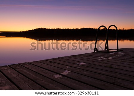 Night swim dock and calm lake at twilight with wet footprints - stock photo