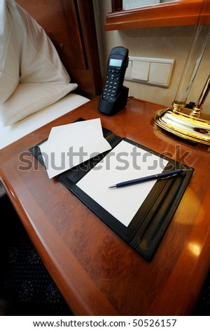 Night table with note book, pen and phone in a hotel room.