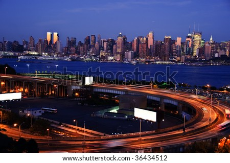night time capture of midtown new york, with white advert space - stock photo