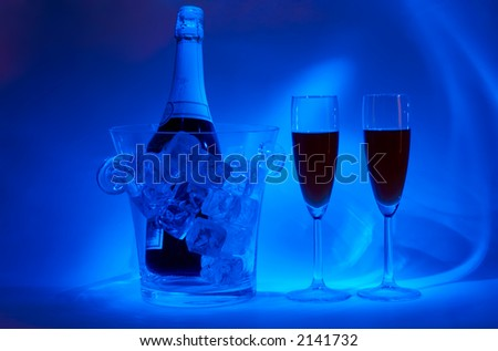 Night-time cellebration (bottle in jar with icecubes and two drinks in special light) - stock photo