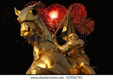 Night time  image of bronze statue of Joan of Arc on Rue de Rivoli in Paris with red fireworks in the background. - stock photo
