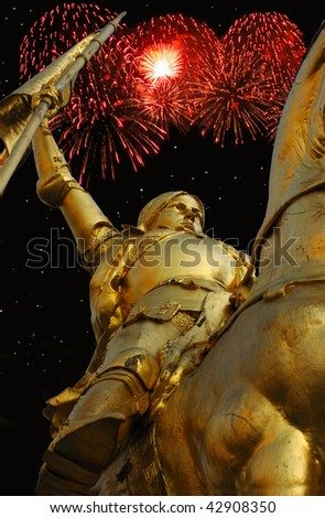 Night time  image of bronze statue of Joan of Arc on Rue de Rivoli in Paris with red fireworks in the background.