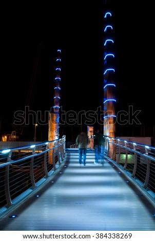 Night time long exposure of two people walking across a modern steel footbridge. Interesting lights and shadow detail, motion blur in people. Taken in Torquay,Devon in the UK. - stock photo
