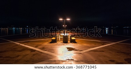 Night time on a lonely pier in Halifax, Nova Scotia.  City lights across historic Halifax harbor.  Night lights shine on empty benches on pier.  Long pier protrudes into harbor.  Halifax at night. - stock photo