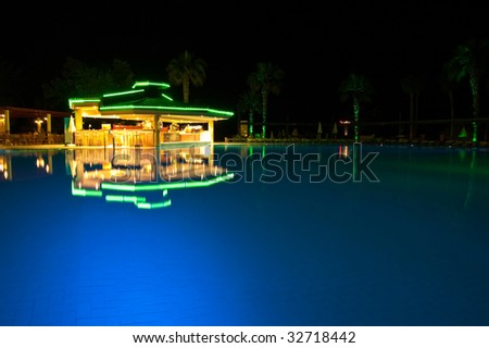 Night time photo of a swimming pool at a tropical resort - stock photo