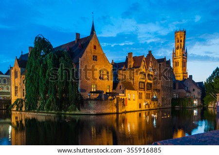 Night time scene of the dock of Rosary - Rozenhoedkaai - and Belfort Tower reflected in canal in Brugge, Belgium
