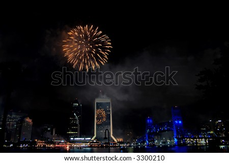 night time view of downtown Jacksonville, Florida with reflections of fireworks - stock photo