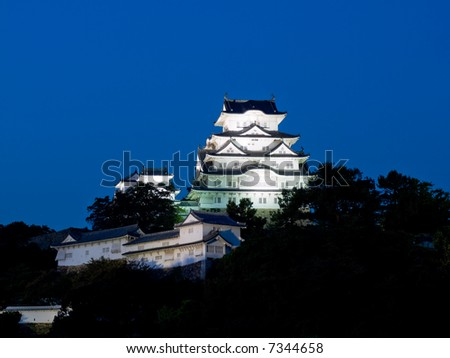 Night time view of the main tower and some of the inner walls of Himeji Castle lit up on the hillside with dark shapes of the trees of the castle grounds around the base of the hill - stock photo