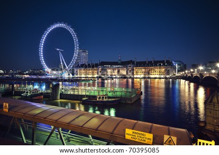 Night time view of the South Bank of the Thames, London including the London Eye, County Hall and Westminster Millennium Pier - stock photo